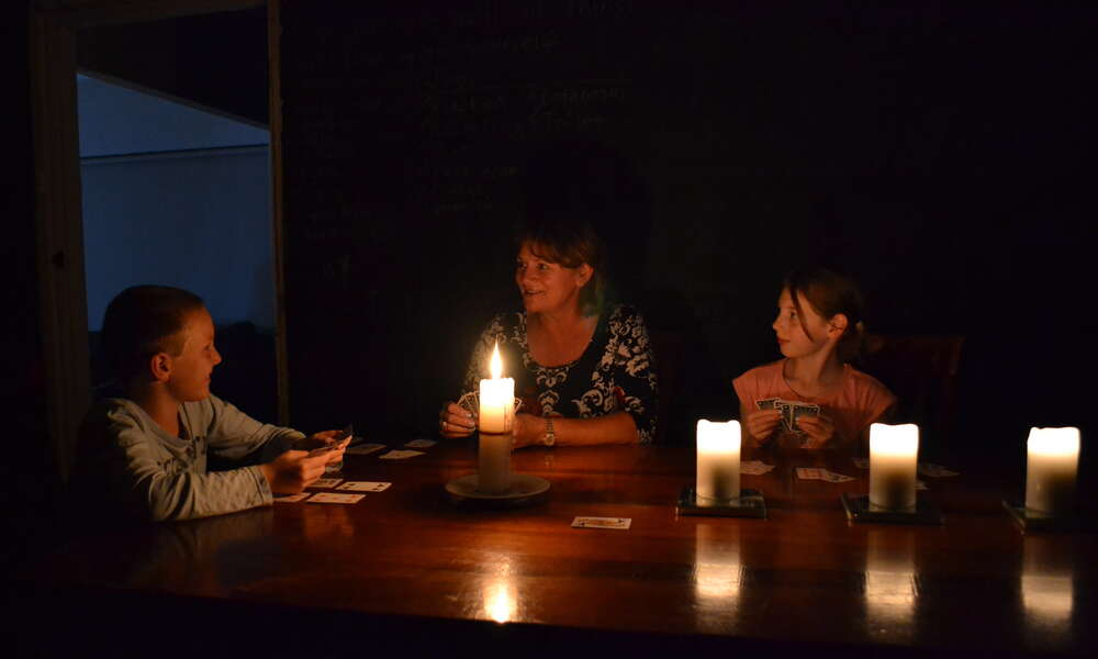 Peter Izzard, Margot Dunne and Bethany Izzard play cards by candlelight during Earth Hour.
