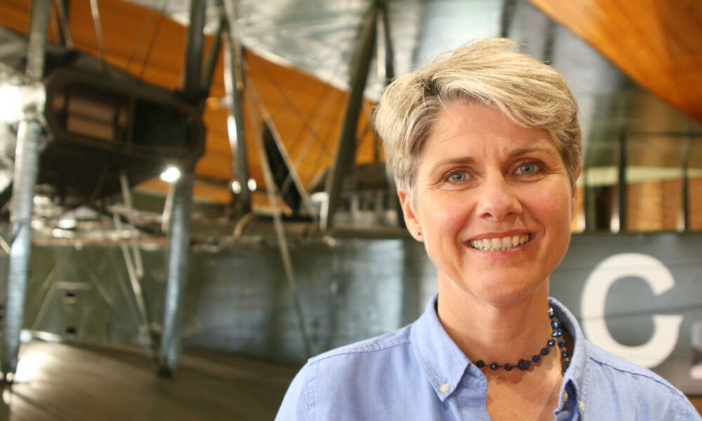 Sunday Mail columnist and author Lainie Anderson stands in front of the Vickers Vimy - the same open cockpit biplane that won the 1919 Great Air Race and the feature of her book 'Long Flight Home'.