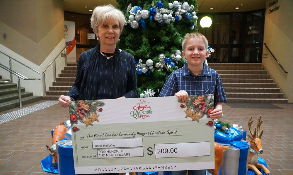 10 year old Jacob Halleday (right) donated his savings of $209 to the appeal to help others during the festive period.