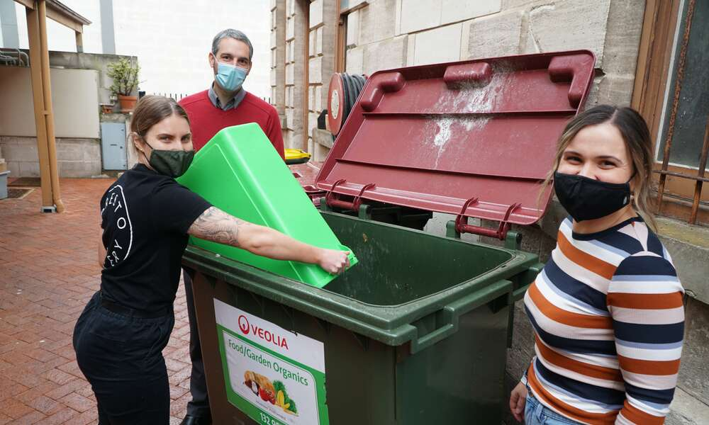 City of Mount Gambier Sustainability Officer Aaron Izzard, Presto Eatery Head Chef Kathryn Holmes and Manager Kate Wilson empty food waste into the skip bin as part of the food waste diversion trial.