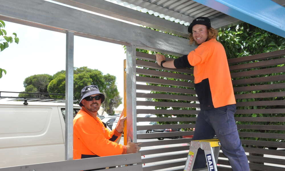City of Mount Gambier outdoor staff Shaun Horrigan and Sam Egan erect one on the bus shelters on James Street Mount Gambier.