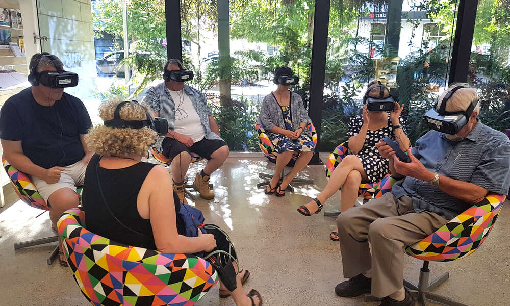 Participants take part in the exclusive preview of virtual reality work, Collisions at the Main Corner.